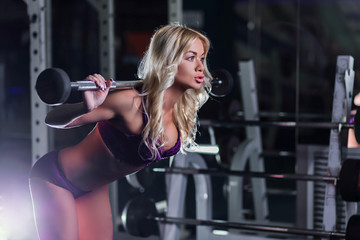 very beautiful, sexy blonde girl with a slender figure, tanned skin in purple lingerie squats with dumbbells on the hands, profile, cute face, horizontal, in a gym, fitness club, cross fit