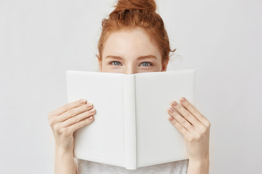 Portrait of ginger girl hiding behind book looking at camera.