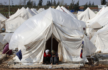 Syrian refugees chat in front of a tent at Reyhanli refugee camp in Hatay