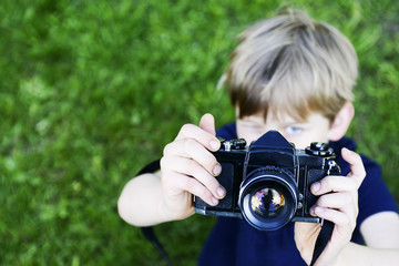 Little child blond boy with an old camera shooting outdoor. Kid taking a photo using a vintage retro film camera. Green summer grass lawn background.