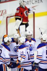 Calgary Flames' goalie Miikka Kiprusoff  stands in the background while Edmonton Oilers' Sam Gagner (L) Ryan Smyth , Jordan Eberle, Jeff Petry  and Ladislav Smid