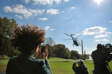 A woman takes pictures with her mobile phone as Marine One helicopter transporting U.S. President Barack Obama leaves he South Lawn of the White House during his departure to Fayetteville, North Carolina, in Washington, U.S.