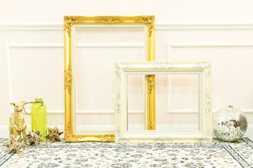 Vintage blank golden and white wooden frames and decorative things on floor with white wall background.