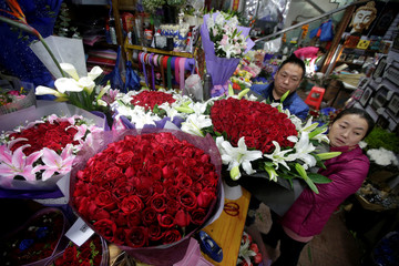 Vendors pack a bunch of red roses for upcoming Valentine's Day in Beijing