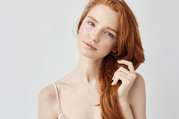 Portrait of tender beautiful girl with red hair smiling looking at camera.