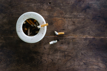 cigarette with ashtray on wood table.