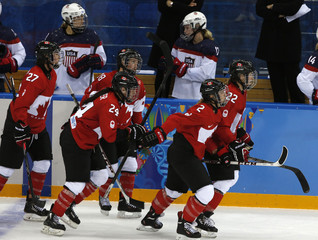 Canada's Meghan Agosta-Marciano (2) and her linemates skate to the bench after her goal against Team USA during the third period of their women's preliminary round hockey game at the Sochi 2014 Winter Olympic Games