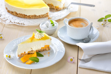 Kuchen ohne Backen: Mango-Frischkäsekuchen mit Boden aus Kekskrümeln, dazu eine Tasse Kaffee mit Crema  - Mango cheesecake  from the refrigerator without baking, served with a cup of coffee