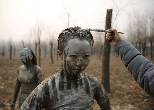 """A staff paints a model with camouflage colours to blend her in with the background for Chinese artist Liu Bolin's artwork """"Dongji"""", or Winter Solstice, in Beijing"""