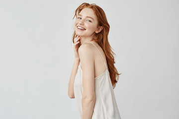 Beautiful redhead girl with freckles smiling posing.
