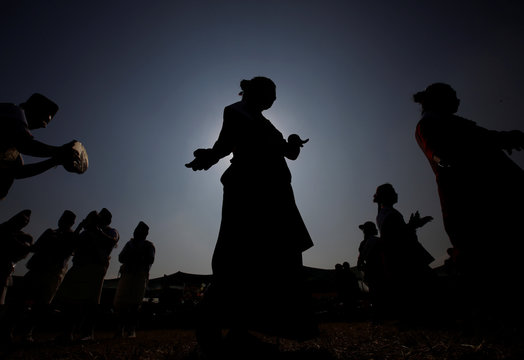 A Gurung girl wearing a traditional costume is silhouetted against the sun as she dances while taking part in their Tamu Lhosar parade in Kathmandu