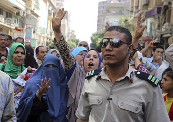 Relatives and families of supporters of ousted President Mursi do the Rabaa sign near  security forces at a court in Minya