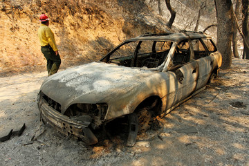 Tom Stokesberry with the U.S. Forest Service walks past a destroyed car after the Soberanes Fire burned through the Palo Colorado area, north of Big Sur, California