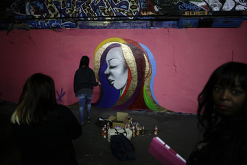 An artist who calls herself Hazard paints during a graffiti art event in support of Breast Cancer Care in London