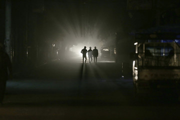 Men walk along a street at night in eastern al-Ghouta, near Damascus