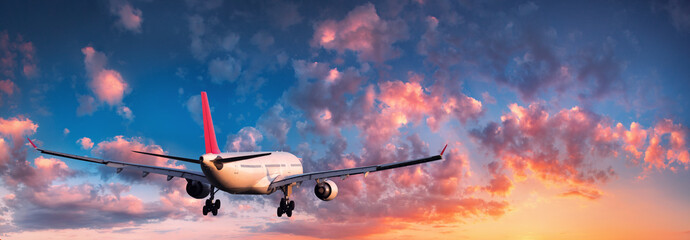 Airplane. Landscape with big white passenger airplane is flying in the blue sky with red and orange clouds at colorful sunset. Travel. Passenger airliner. Business trip. Commercial plane. Aircraft Wall mural