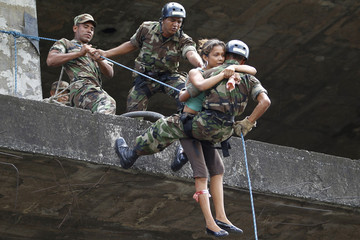 Soldiers evacuate a student acting as an injured person during an earthquake rescue drill in Managua