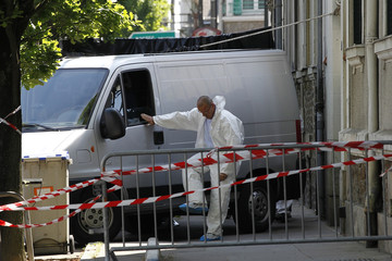 A crime scene investigator works outside the house where human body parts were found in Nantes