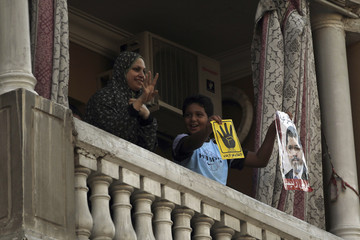 Supporters of Muslim Brotherhood and ousted President Mursi shout slogans against military and interior ministry as they hold posters of Mursi and the Rabaa symbol, from balcony, at rally near Giza square, south of Cairo
