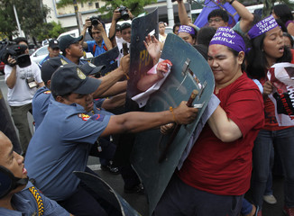 Riot policemen use their shields to push back anti-U.S. protesters from women's group Gabriela outside the U.S. Embassy in Manila