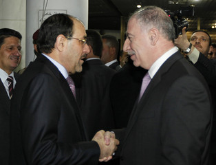 Iraqi parliament speaker Osama al-Nujaifi shakes hands with Iraq's Prime Minister Nuri al-Maliki, upon his arrival at the parliament building in Baghdad