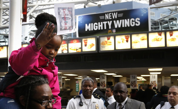 A girl throws a protest flier during a rally in support of higher pay for low-wage earners in a McDonald's restaurant inside the National Air and Space Museum in Washington