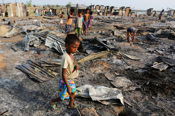 A boy walks among debris after fire destroyed shelters at a camp for internally displaced Rohingya Muslims in the western Rakhine State near Sittwe