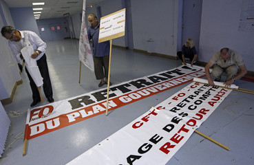 French FO labour union activists prepare placards and banners before a protest march over pension reforms in Marseille