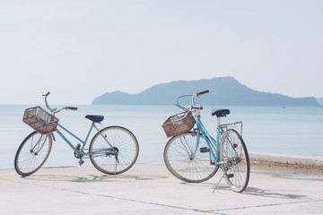 vintage bicycle on concrete road   beach over blue sea and clear blue sky background, spring or summer holiday vacation concept.soft focus