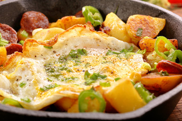 fried egg and baked potatoes with sausage chorizo on frying pan