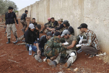 Rebel fighters treat the wounds of their fellow fighters during what they said was an offensive against forces loyal to Syria's President Bashar al-Assad around Handarat area, north of Aleppo in an attempt to regain control of the area