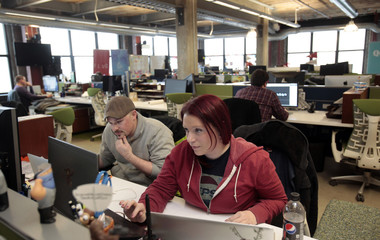 Entrepreneurs Doig and Lareau, work on their web businesses in the M@dison building owned by Quicken Loans founder Gilbert, in downtown Detroit