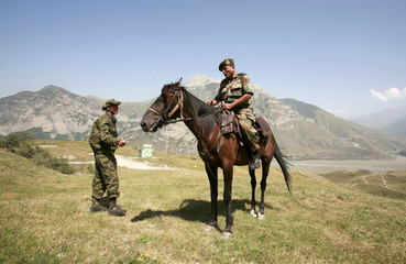 An Indian army officer rides a horse with the assistance of a Russian serviceman during a visit to a range outside Vladikavkaz