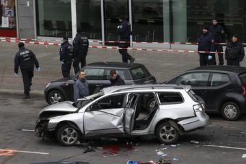 Police inspect a damaged Volkswagen car in the Bismarckstrasse in Berlin