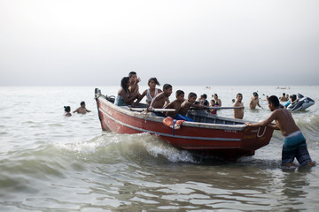 Beachgoers sit in boat during summer day at Agua Dulce beach in Lima's district of Chorrillos