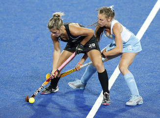 New Zealand's Gunson challenges Argentina's Sruoga during their women's Group B hockey match at the London 2012 Olympic Games at the Riverbank Arena on the Olympic Park