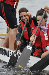 Britain's Catherine, the Duchess of Cambridge, paddles a dragon boat as she races against her husband Prince William on a lake in Dalvey by-the Sea