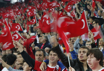 Turkey supporters wave flags before 2014 World Cup qualifying soccer match between Turkey and Netherlands in Istandbul