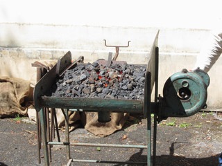 Old-fashioned blacksmith furnace with burning coals for iron work