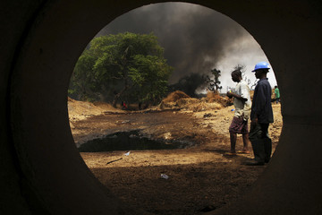 Workers, seen through a pipe, look on at the scene of an oil pipeline fire in Dadabili, Niger state