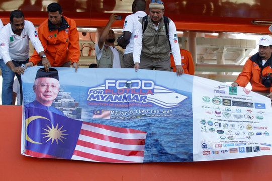 Men display a banner while Malaysian NGO's aid ship carrying food and emergency supplies for Rohingya Muslims arrives at the port in Yangon