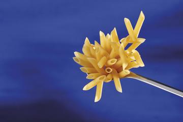 Foto Still life verticale di maccheroni, penne pasta di grano duro su cucchiaio di acciaio, piano di acciaio con pasta. Sfondo blu sfumato