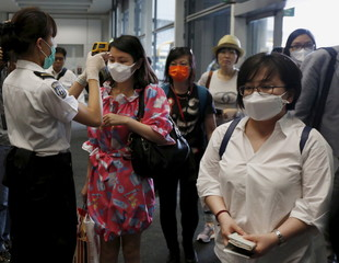 Flight passengers from Busan, South Korea, receive a temperature check upon their arrival at Hong Kong Airport in Hong Kong