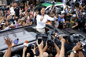 Peru's presidential candidate Keiko Fujimori gestures to supporters and media as she holds her I.D. after voting during presidential election in Lima