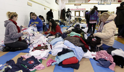 Volunteers sort through donated clothing brought to be given to residents in need at the Belmar Municipal Complex in Belmar