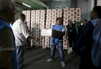 A postal worker carries a ballot box to load onto a truck for delivery ahead of Sunday's presidential election in Buenos Aires