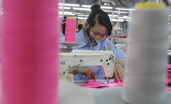 A woman works on the assembly line of a shoe factory in Tan Lap village