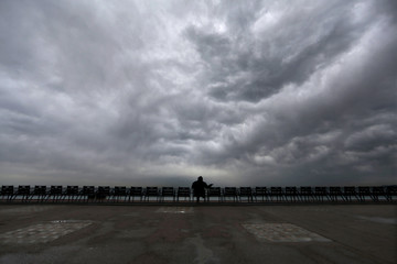 A man sits on a chair as dark clouds gather over the promenade des Anglais during a rainy day in Nice
