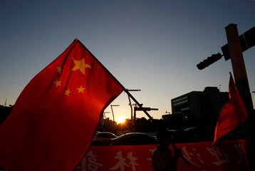 A pro-China supporter holds Chinese national flag, outside the dinner venue of Sha Hailin, a member of Shanghai's Communist Party standing committee, in Taipei, Taiwan