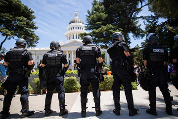Sacramento Police officers gather after multiple people were stabbed during a clash between neo-Nazis holding a permitted rally and counter-protestors on Sunday at the state capitol in Sacramento.